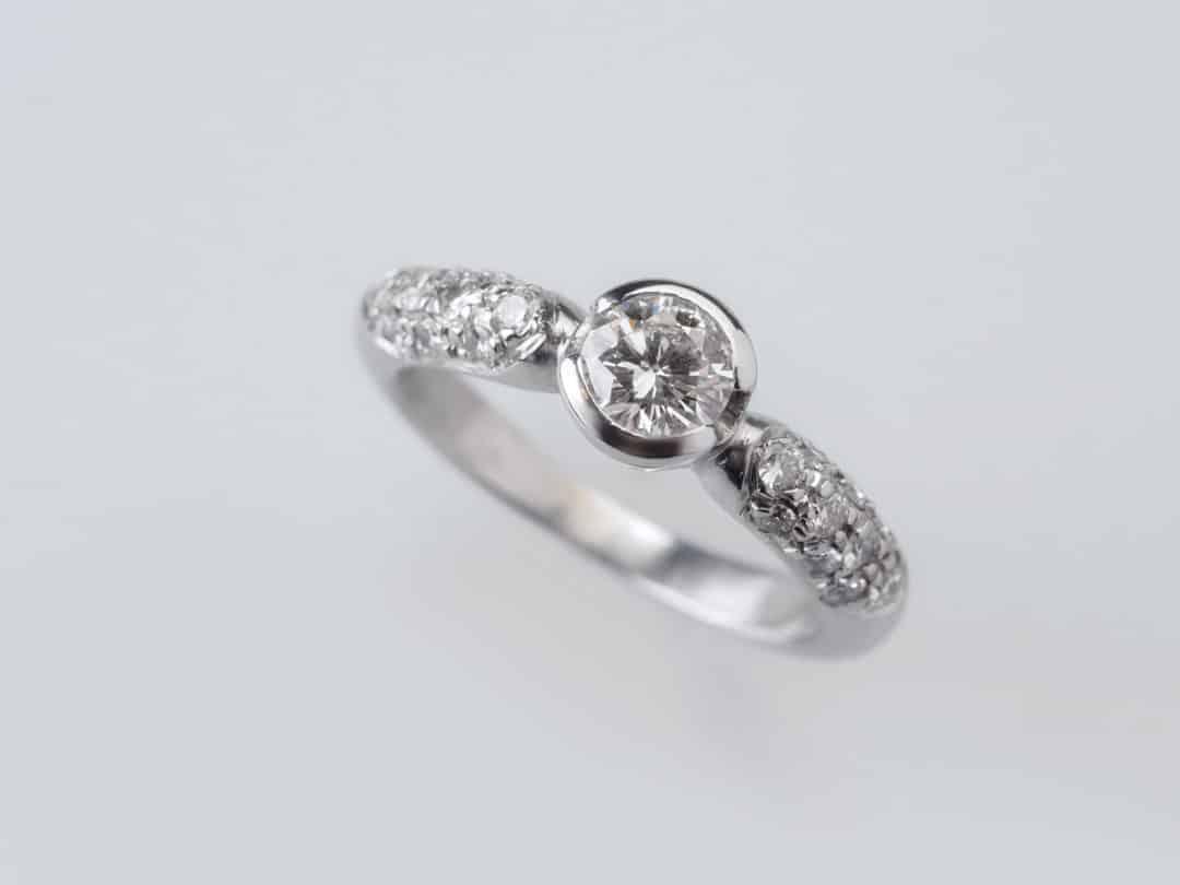 Anello in oro bianco con diamante centrale e pavè